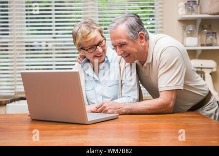 Senior Paar mit dem Laptop zusammen zu Hause in der Küche - Stockfoto