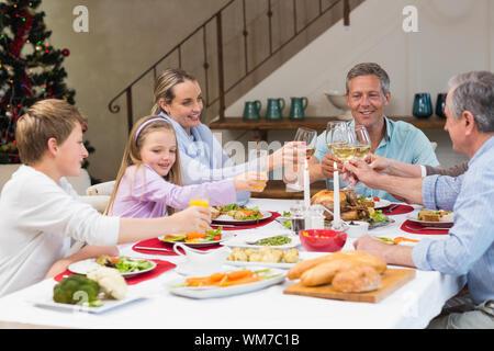 Familie Toasten mit Weißwein in einem Weihnachten Abendessen zu Hause im Wohnzimmer - Stockfoto