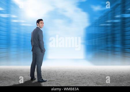 Lächelnd Geschäftsmann stehend gegen Server Flur in Wüste Einstellung - Stockfoto