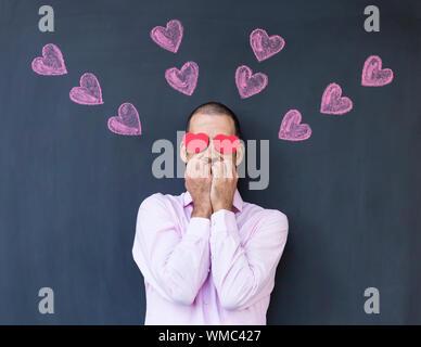 Mann mit Herz Form Papier auf die Augen gegen Tafel stehend - Stockfoto