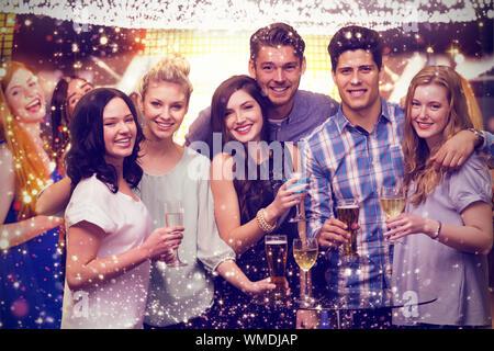 Freunde mit Getränken gegen Gold und Rot leuchtet - Stockfoto