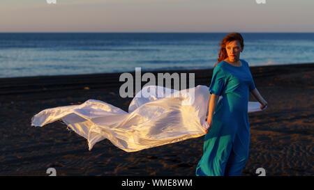 Frau mit Stoff stehen am Strand bei Sonnenuntergang gegen Sky - Stockfoto