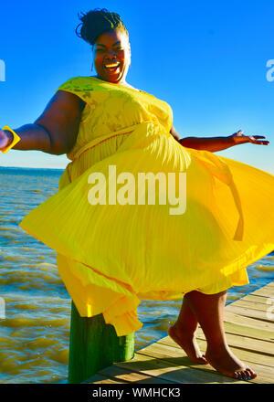 Lächelnde Frau im gelben Kleid sitzt am Strand - Stockfoto