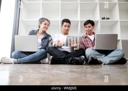 Glückliche junge Freunde mit Laptops beim Sitzen auf dem Boden - Stockfoto
