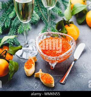 Leckere Blätterteig Törtchen in der Form von Fisch mit rotem Kaviar auf einem festlich gedeckten Tisch mit Gläsern der Champagner. - Stockfoto