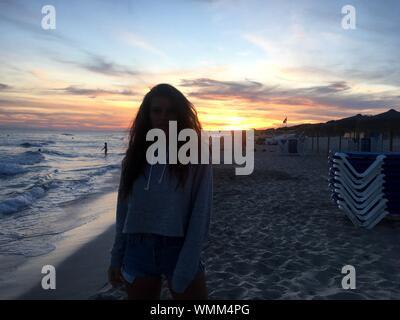 Porträt der Frau, die am Strand gegen Himmel bei Sonnenuntergang - Stockfoto