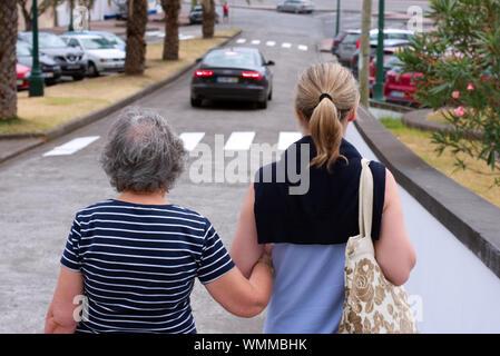 Erwachsene Tochter helfen alte Mutter mit Rohrstock im