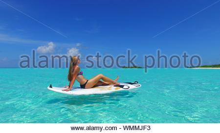 Seitenansicht des Jungen Bikini Frau sitzt auf der Paddleboard im Meer - Stockfoto