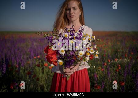 Frau mit lila Blüten. Schöne rothaarige Mädchen in ein blühendes Feld Genießen Sie Freiheit und Ruhe - Stockfoto
