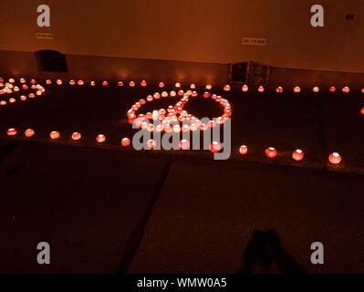 Hohen Winkel Blick auf das beleuchtete Jack O Laternen arrangiert in Frieden Symbol auf dem Bürgersteig in der Nacht - Stockfoto