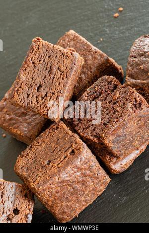 Kleines Quadrat Schneiden Chocolate Brownies al krümelig und auf einem schwarzen Schiefer Fach. - Stockfoto