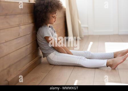 Schwarz cute kid Mädchen allein sitzen auf dem Boden umgekippt. - Stockfoto