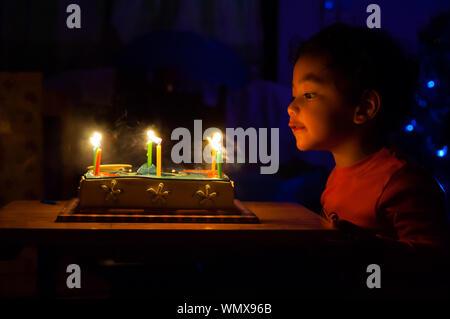 Cute Boy Blasen Geburtstag Kerzen in der Dunkelkammer - Stockfoto