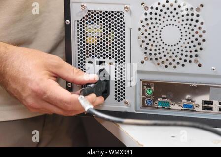 Hand Beilagen Netzkabel in einen Computer ein. - Stockfoto