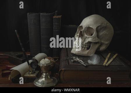 Close-up des menschlichen Schädels mit Kreuz auf Buch am Tisch - Stockfoto