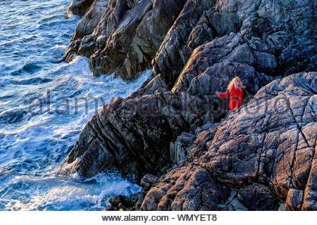 Blonde Frau auf Felsen und beobachtete, Wellen, Lighthouse Park, West Vancouver, British Columbia, Kanada - Stockfoto