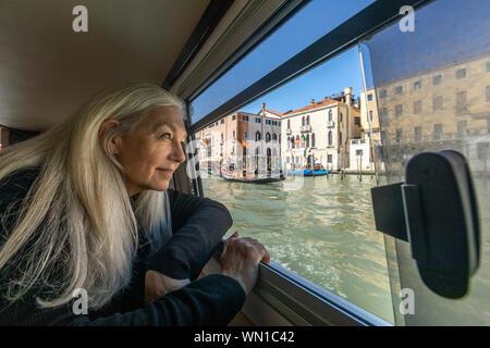 Frau, die von Boot-Fenster auf den Canal Grande, Venedig, Italien - Stockfoto