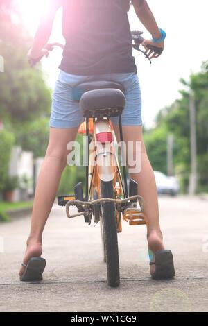 Niedrige Abschnitt von Frau Reiten Fahrrad auf der Straße - Stockfoto