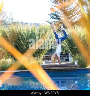 Junge Frau Stretching Swimmingpool - Stockfoto