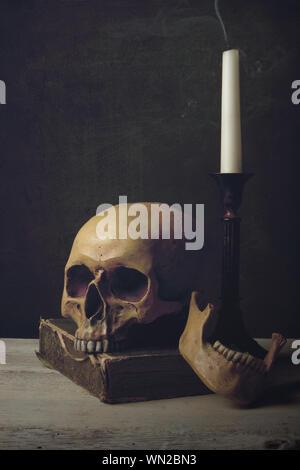 Nahaufnahme des menschlichen Schädels mit Kerze und Buch auf Tabelle - Stockfoto