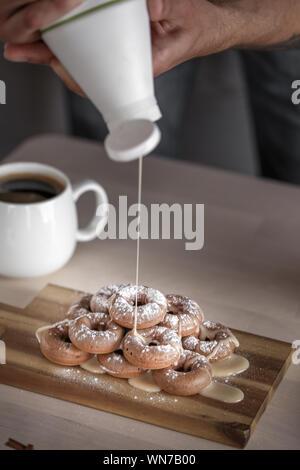Zugeschnittenes Bild des Menschen gießen Karamell auf Donuts in der Küche - Stockfoto