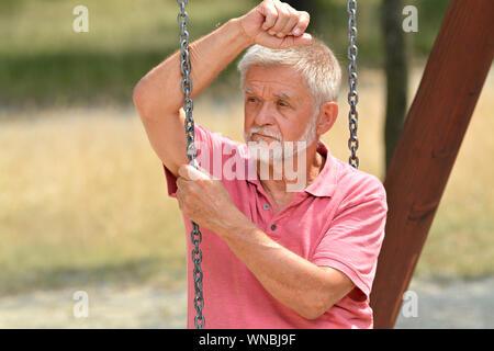 Älterer Mann sitzt auf Kind Schwingen - Stockfoto