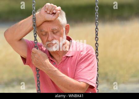Einsamen alten Mann auf Swing - Stockfoto