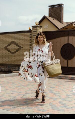 Ein vertikaler gerne attraktive Frau in einem Kleid mit Blüten mit einem großen Korb Tasche posing - Stockfoto