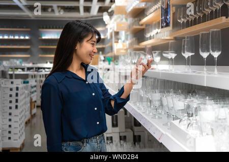 Asiatische Frauen werden neue Glas in der Mall zu kaufen. Einkaufsmöglichkeiten für Lebensmittel und Haushaltswaren sind in Märkte, Supermärkte oder großen Shopping Centr erforderlich - Stockfoto