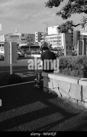 MATSUYAMA, Japan - 16.August 2019: Eine vertikale geschossen von einer Person in der Nähe der Straße sitzen mit Autos und Gebäude - Stockfoto