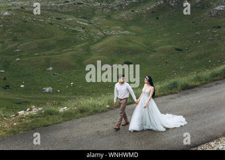 Die Braut und der Bräutigam werden auf der Straße in den Highlands. Hochzeit in den Bergen.