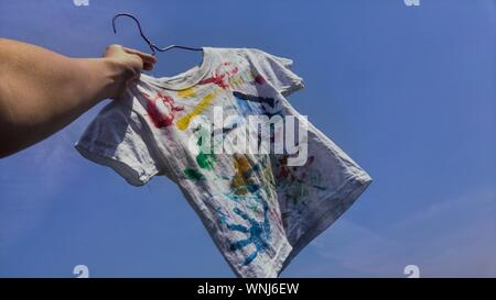Low Angle View der Hand Holding Kind gemalt T Shirt - Stockfoto