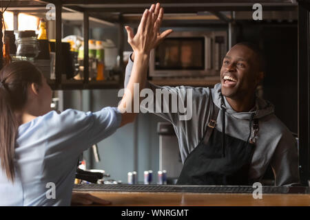 African American barista hoch fünf mit Frau an der Arbeit aufgeregt - Stockfoto