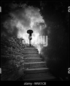 Frau auf Treppe mit Schirm im Regen - Stockfoto