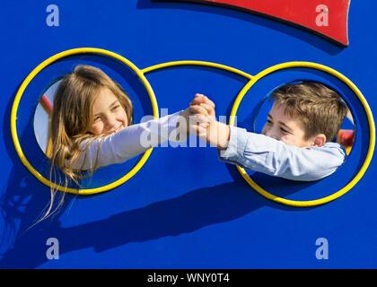 Junge und Mädchen berühren mit der Hand. Kinder stellen Kopf durch die Bohrung am Spielplatz. Paar junge Kinder liebe. Liebe und Freundschaft Konzept. Stockfoto
