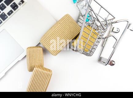 Miniatur Warenkorb und Kartons schwappte über Laptop auf weißem Hintergrund - Stockfoto