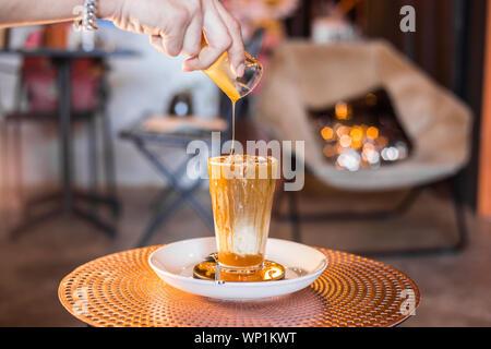 Eiskaffee mit Milch in hohe Gläser auf dem Tisch mit Karamell Sirup auf gegossen. - Stockfoto