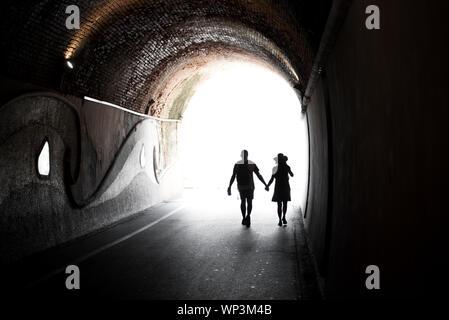 Paar Hand in Hand durch eine gewölbte Tunnel oder Unterführung gegen das helle Licht am Ende in einem konzeptionellen Bild Silhouette - Stockfoto