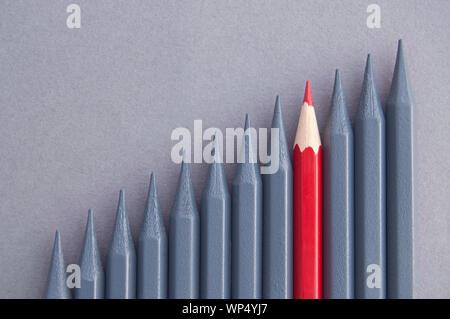 Roter Stift in der Mitte stehend unter Grau Bleistifte - Stockfoto