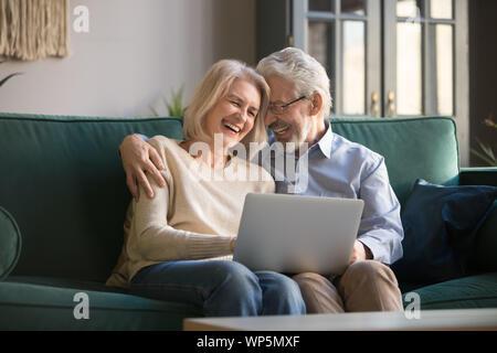 Ältere grauhaarige Frau, Lachen und Genießen Freizeit mit Computer. - Stockfoto