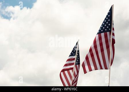 Zwei amerikanische Flaggen im Wind flattern vor einem strahlend blauen Himmel mit flauschigen weissen Wolken. - Stockfoto
