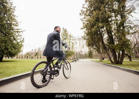 Tausendjährige afro Geschäftsmann Reiten Fahrrad im Park zu arbeiten - Stockfoto