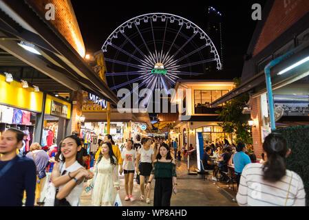 Bangkok, Thailand - 28. Juli 2019: einem überfüllten Gänge an Asiatique sun der Riverfront in der Nacht, mit Blick auf das Riesenrad. - Stockfoto