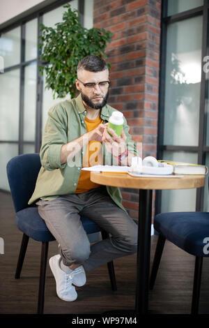Unternehmer Tragen einer Brille holding Pack von Vitaminen - Stockfoto