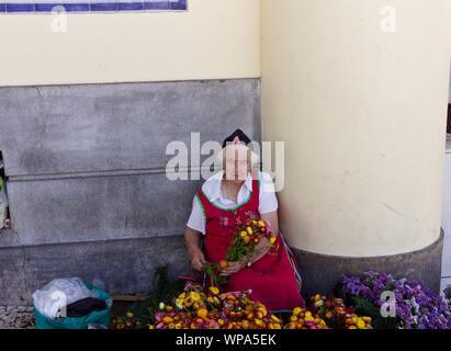 Funchal, Madeira, Portugal - 16 August 2019: Eine alte Blume Verkäufer in den Straßen von Funchal mit einem Madeira traditionelles Kleid - Stockfoto