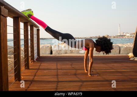 Glückliche junge afrikanische Frau dehnen und Aufwärmen vor einem Outdoor Training. Das Mittelmeer im Hintergrund Stockfoto