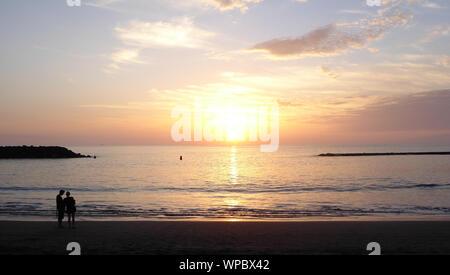 Paar beobachten Sonnenuntergang am Strand