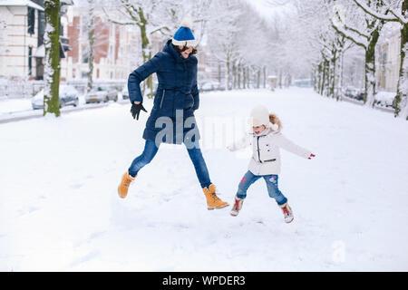 Schöne Mädchen tragen in Jeans, weiße Daunenjacke und Strickmütze springen mit Mama im Schnee draussen. Spaß haben. Winter Saison. Kindheit. Fa - Stockfoto