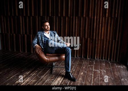 Junge erfolgreiche Geschäftsmann in einem blauen Anzug in einem Käfig sitzt in einem Ledersessel. junger Mann mit einem Bart lächelnd - Stockfoto