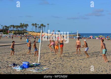 Gruppe junger Männer spielen Beachvolleyball am Strand Arenal in Javea an der Costa Blanca, Spanien. Am späten Nachmittag im Sommer